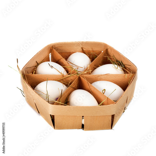 eggs in a wooden container isolated on white