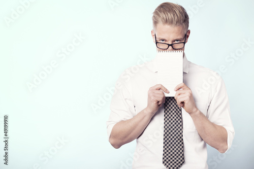 Young businessman presenting blank notepad.
