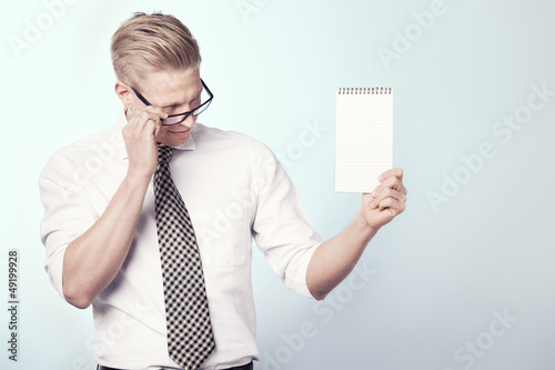 Likable businessman looking at empty notebook.