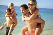 Two young guys piggybacking their girlfriends on the beach