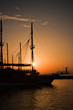 Sailing ship silhouetted against amber setting sun