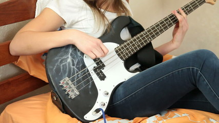 Young Girl Playing Bass Guitar At Home