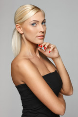 Beautiful blond woman standing with hand on chin