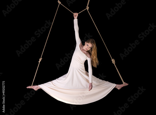 Young woman gymnast in white dress on rope