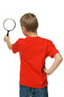 Back viev of 6 years boy looking through the magnifying glass