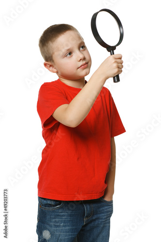 6 years boy looking through the magnifying glass