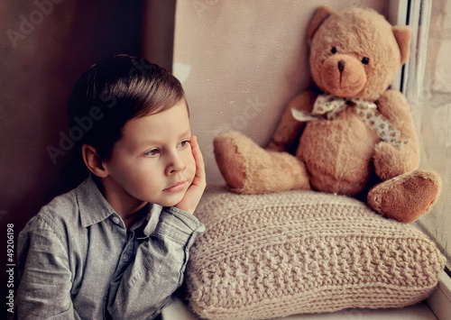little boy with a toy on a knitted pillow looking out the window