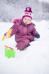 Adorbale girl dig snow with showe and pail on playground covered