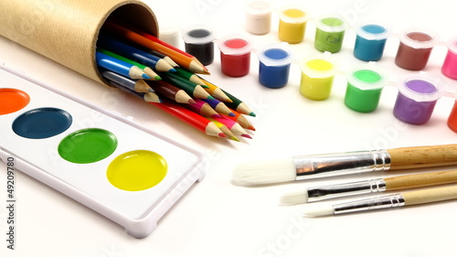 Colored pencils, paint brushes, and paint supplies