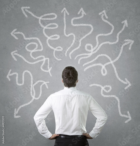 Confused businessman looking at many twisted arrows