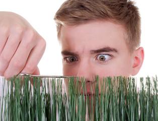 Teenager schneidet Gras mit Schere