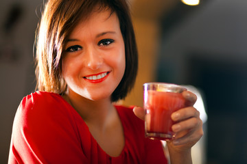 Smiling woman drinking a cocktail