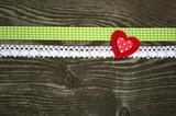 Klebeherz auf Holzbrett mit Schleifenbändern