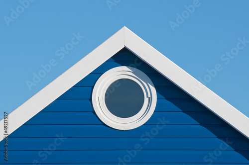 round window in blue beach hut gable