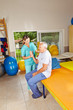 Senior macht Krankengymnastik im Sitzen