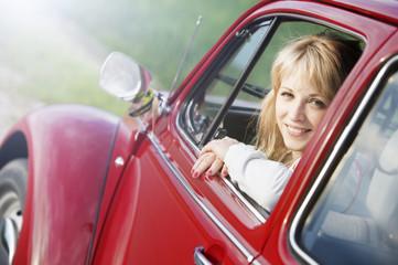 Beautiful woman in red car.