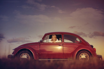 Red Volkswagen Beetle with beautiful woman inside.