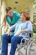 Ältere Patientin im Rollstuhl mit Krankenschwester