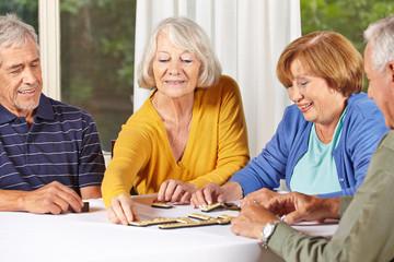 Gruppe von Senioren spielt Domimo