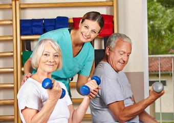 Senioren heben Hanteln bei Physiotherapie