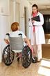 Seniorin im Rollstuhl redet mit Ärztin