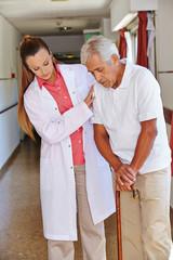 Krankenschwester hilft Senior mit Gehstock