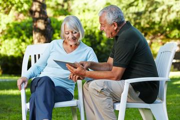 Zwei Senioren mit Tablet PC im Garten