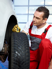 Car mechanic checks the tread pattern of a winter tire
