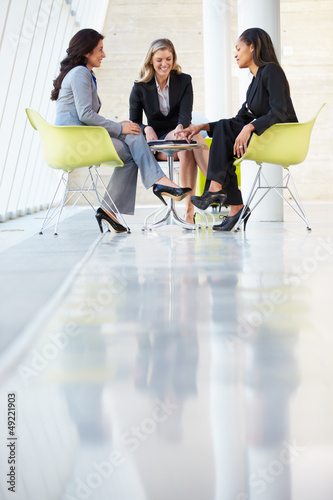 Three Businesswomen Meeting Around Table In Modern Office