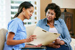 Nurse Discussing Records With Senior Female Patient at Home