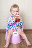 Small baby girl, is sitting on a pink pot and drinks water