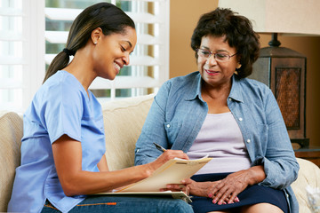Nurse Making Notes During Home Visit With Senior Female Patient