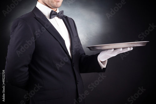 Image of a young waiter holding an empty dish on black backgroun