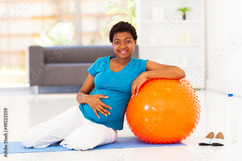 pregnant african american woman with exercise ball at home
