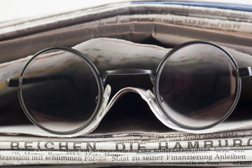 Zeitungen mit Brille