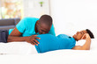 young african american man kissing pregnant wife's belly on bed