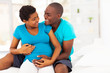 happy african american pregnant woman and husband hugging on bed