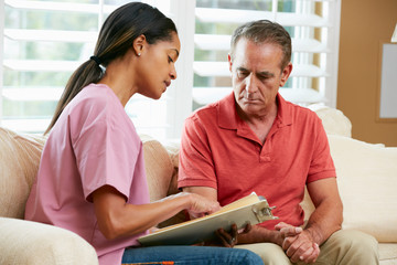 Nurse Discussing Records With Senior Male Patient at Home