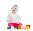 baby girl playing with toys while sitting on floor, isolated ove