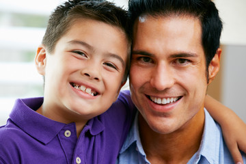 Portrait Of Father And Son Sitting On Sofa At Home