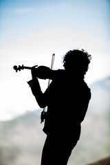 violinist silhouetted on volcano