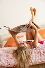 Woman Relaxing On Bed Reading Newspaper