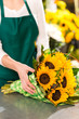 Florist preparing sunflowers bouquet flower shop assistant