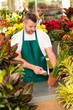 Florist man reading barcode potted plant shop