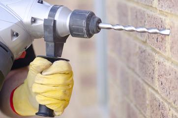 Hand holding drill at wall