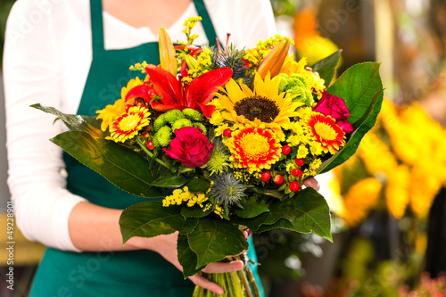 Florist holding bouquet colorful flowers shop assistant