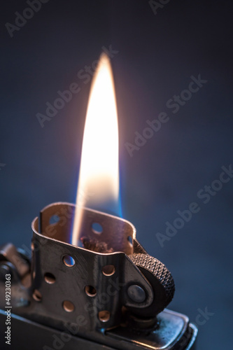Metal lighter on black background with flame.