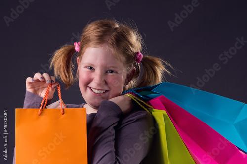 Mädchen mit roten Zöpfen und bunten Taschen