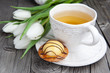 Sweet cake with cup of tea and flowers on wooden table