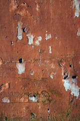 Grungy wall with peeling red paint